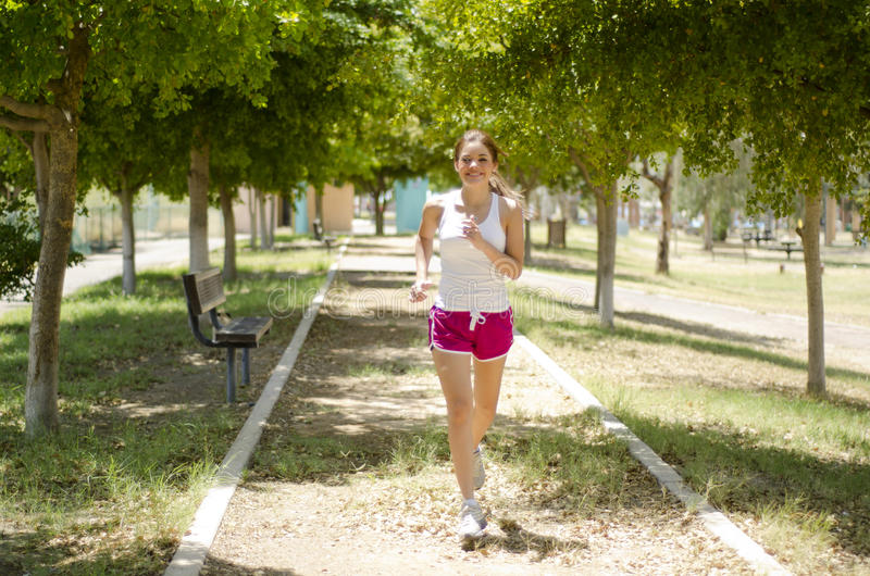 Young woman running at the park. Cute young woman in sporty outfit running at the park stock images