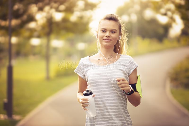 Young woman running in park and listening to music with headphones - Beautiful blonde and fit girl jogging alone outdoor in early royalty free stock photos