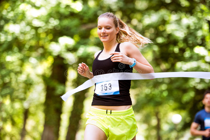 Young woman running the race crossing the finish line. royalty free stock photography