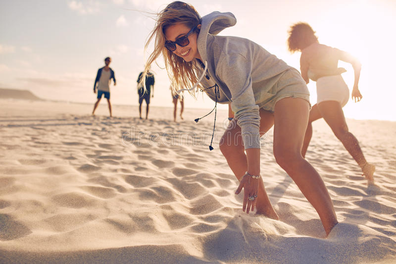 Young woman running race with friends at the beach stock photos