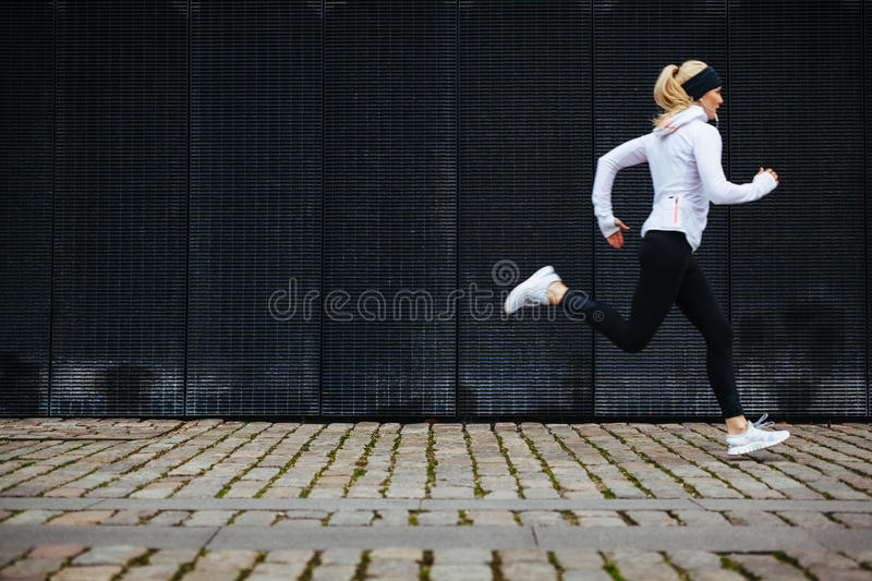 Young woman running on sidewalk in morning. View of young woman running on sidewalk in morning. Health conscious concept with copy space stock photos