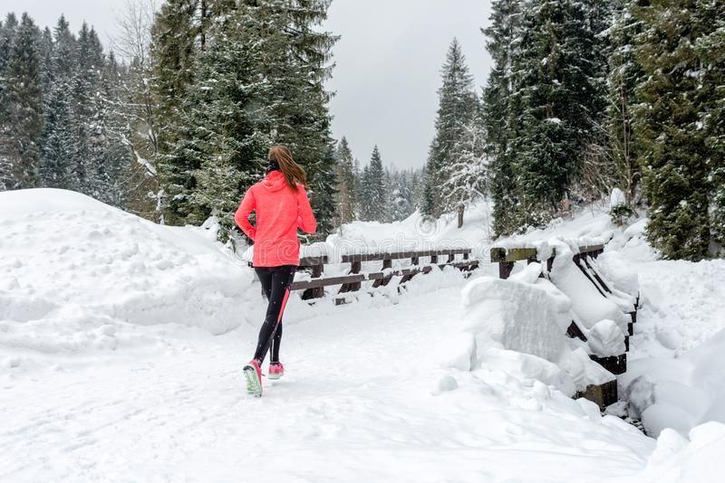 Young woman running on snow in winter mountains wearing warm clothing gloves in snowy weather stock images