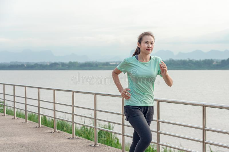 Young woman running on the street with a view of the river in the morning royalty free stock photography