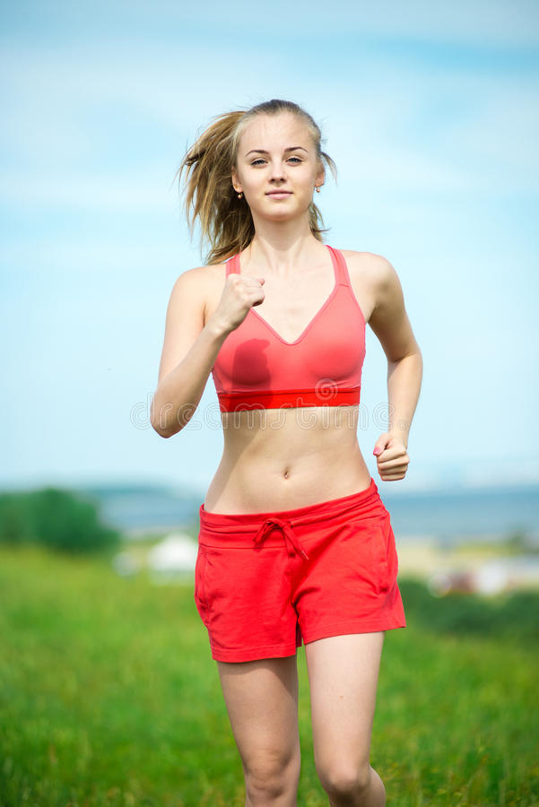 Young woman running summer park rural road stock photography