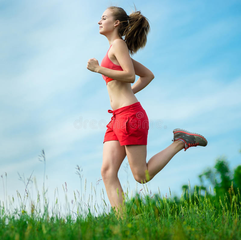 Young woman running summer park rural road. Young lady running. Woman runner running through the summer park rural road. Workout in a park. Beautiful fit girl stock photo