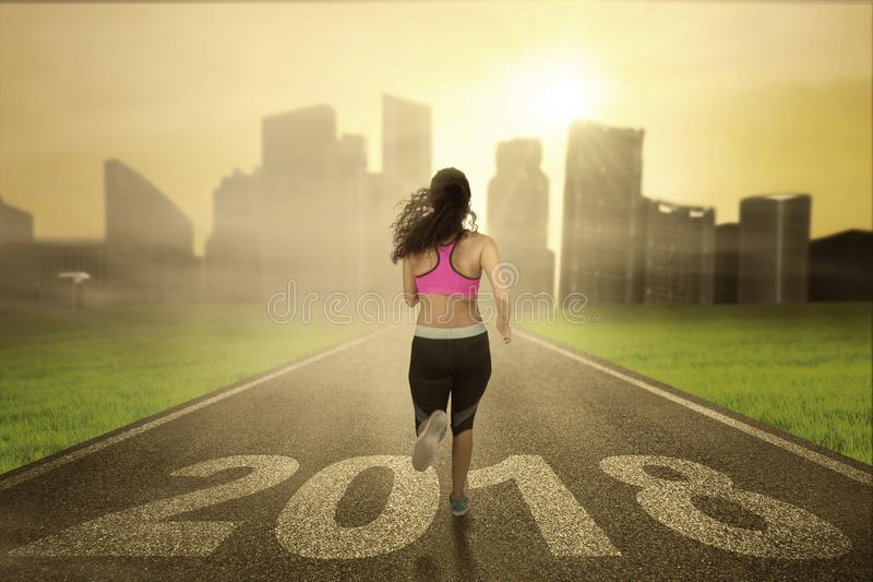 Young woman running toward a city royalty free stock photography
