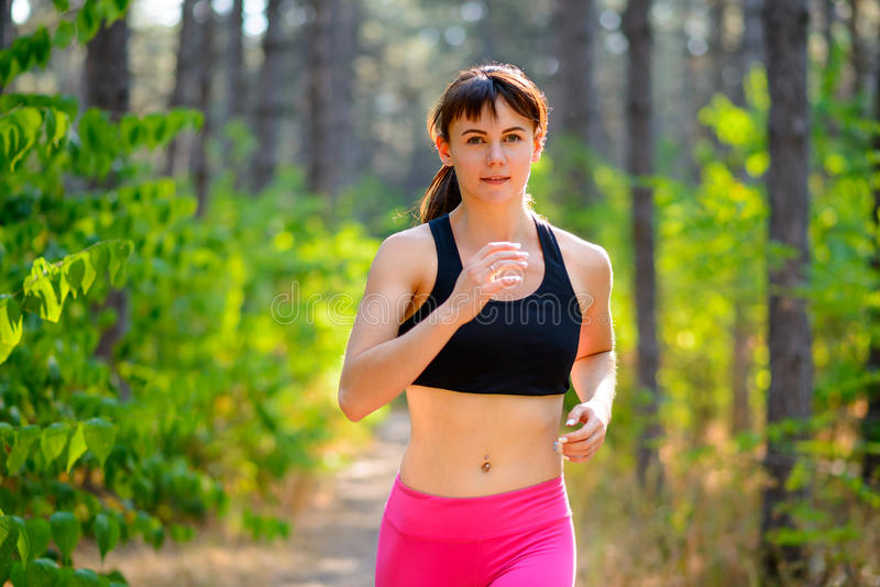 Young Woman Running on the Trail in the Beautiful Wild Forest. Active Lifestyle Concept. Space for Text. Young Woman Running on the Trail in the Beautiful Wild royalty free stock photography