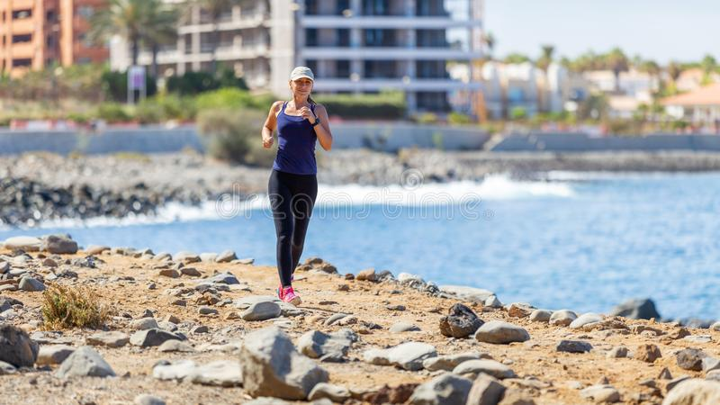 Young woman running on trail near the ocean coast stock photography