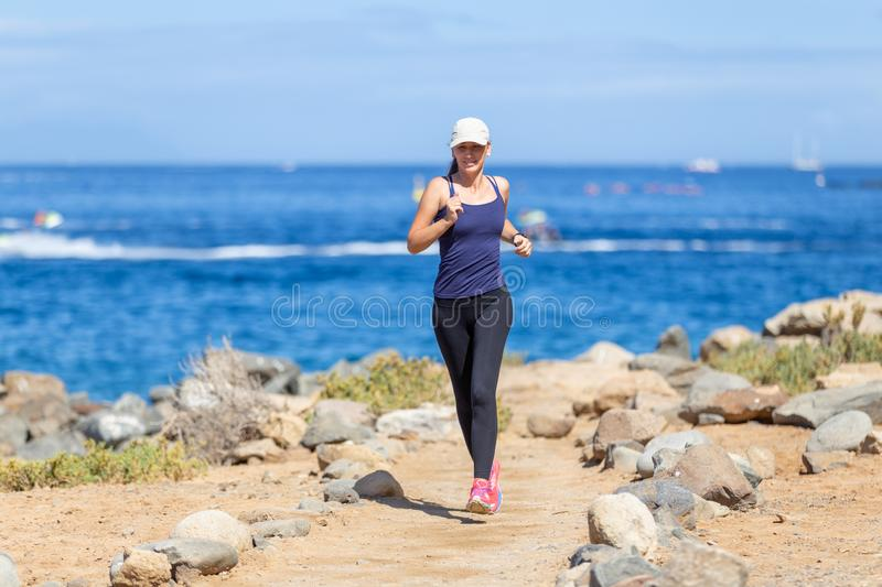 Young woman running on trail near the ocean coast royalty free stock photo