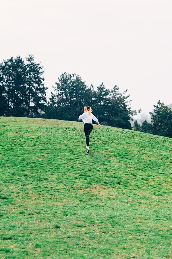 A young woman, running up the hill, romantic or freedom concept stock photos