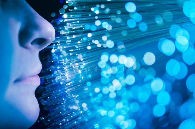Young woman`s face and blue fiber optics stock photography