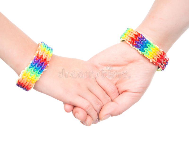 Young woman's hands with a bracelet patterned as the rainbow flag. isolated on white royalty free stock images