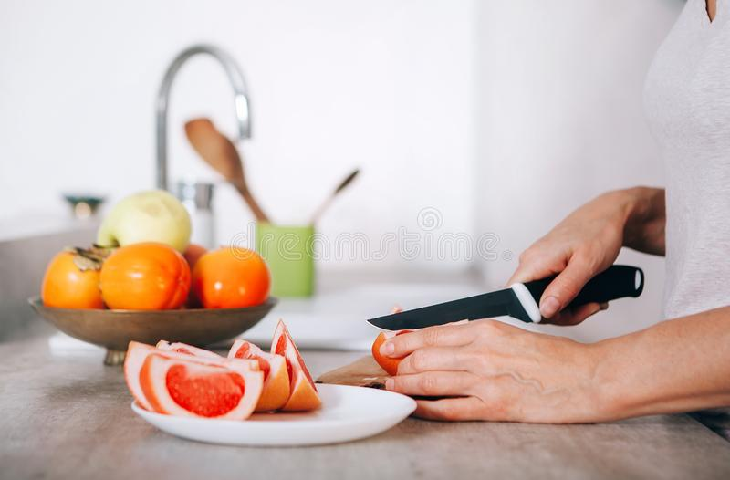 Young woman`s hands chopping grapefruit using a knife and cutting board in modern kitchen close up image. Plenty of apples, stock photo