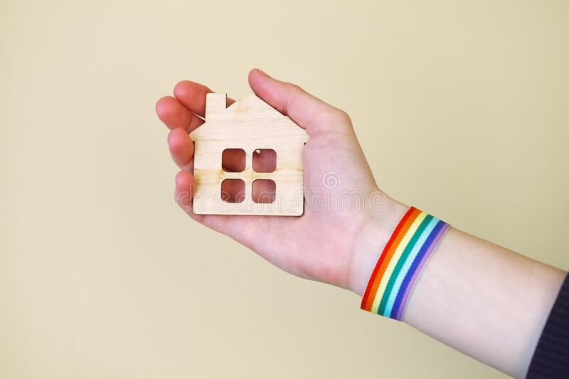 Young woman`s hands holding LGBT colorful rainbow flag wristbands and wooden family house. On yellow background, love, gay pride concept, copy space stock photos
