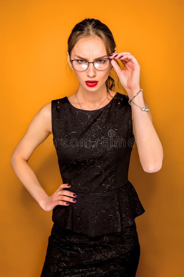 The young woman`s portrait with wary emotions. On orange studio background royalty free stock photography