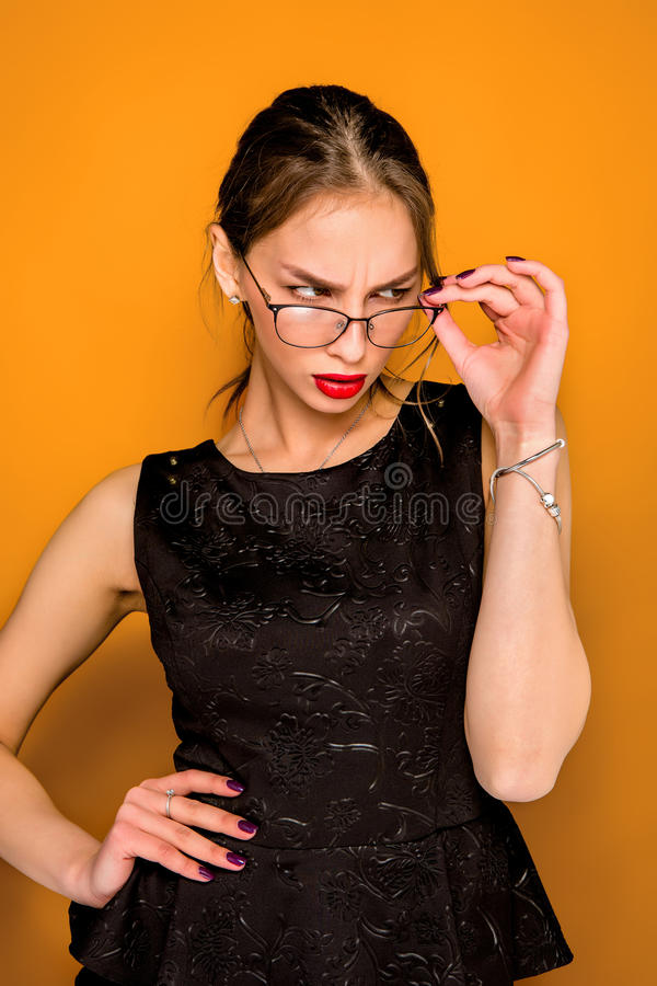 The young woman`s portrait with wary emotions. On orange studio background stock photo