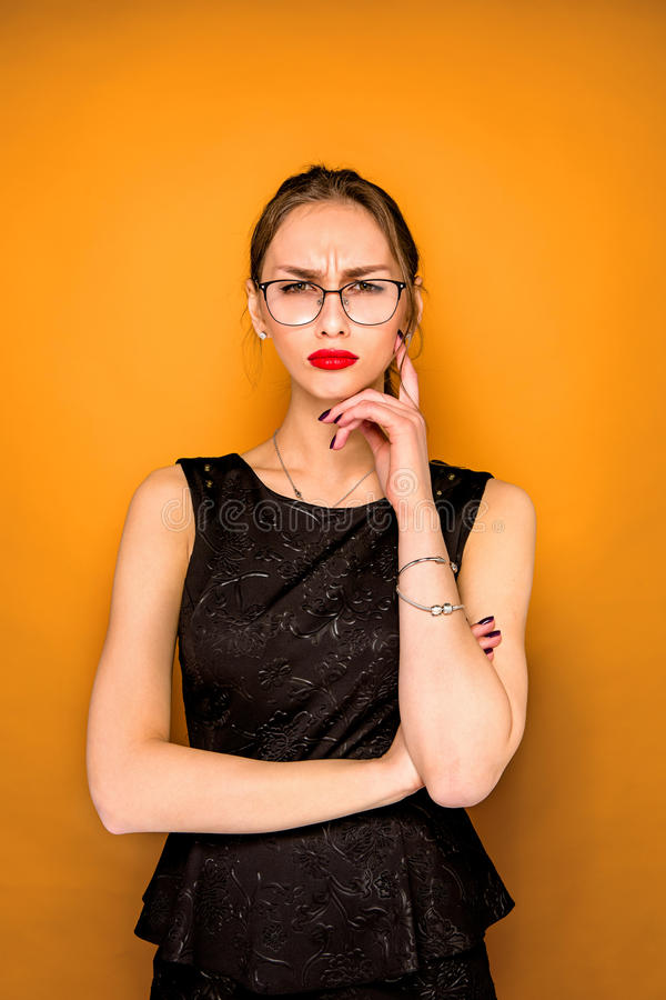 The young woman`s portrait with wary emotions. On orange studio background stock photos