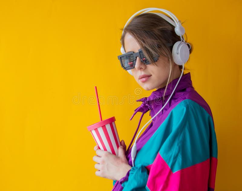 Young woman in 90s style clothes with cup and headphones royalty free stock images