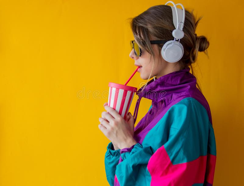 Young woman in 90s style clothes with cup and headphones stock photo