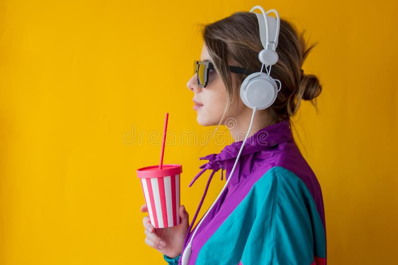 Young woman in 90s style clothes with cup and headphones stock photos
