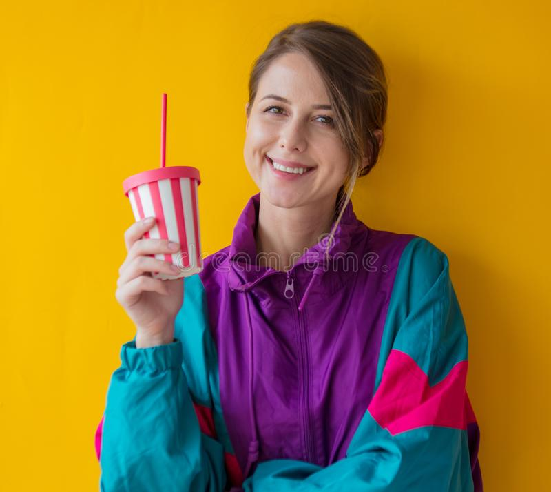 Young woman in 90s style clothes with cup royalty free stock images