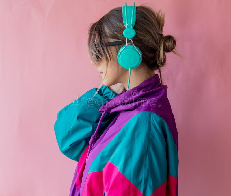 Young woman in 90s style clothes with headphones royalty free stock photography