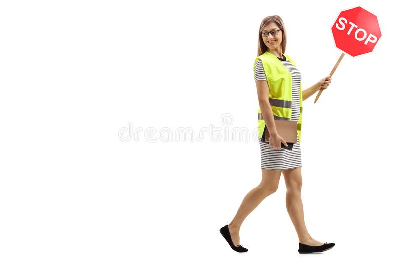 Young woman with safety vest and stop sign walking and looking backwards royalty free stock photography