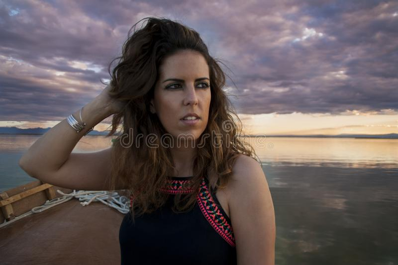 Young woman sailing in a boat on a cloudy day looking at the horizon while she is grooming her hair stock photography
