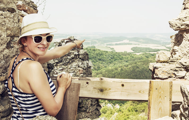 Young woman in a sailor outfit is showing into the distance from. Young caucasian woman in a sailor outfit is showing into the distance from the ruins of the stock photo