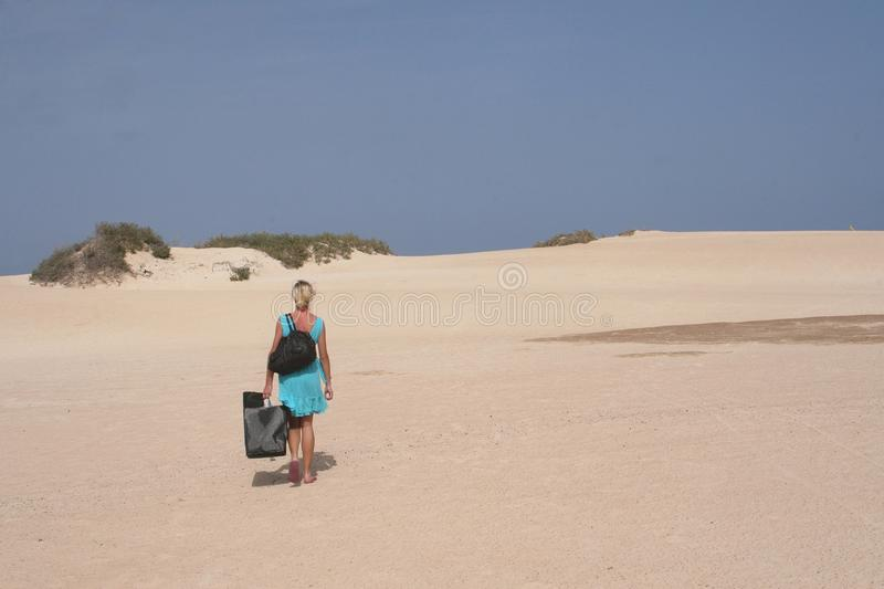 Young woman with bags is hiking in sand-dunes of desert, Fuerteventura, Spain royalty free stock image