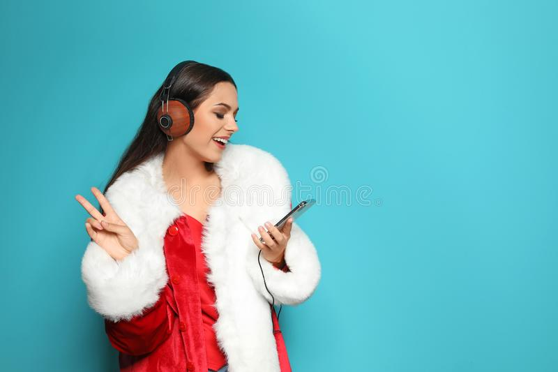 Young woman in Santa costume listening. To Christmas music on color background royalty free stock photos