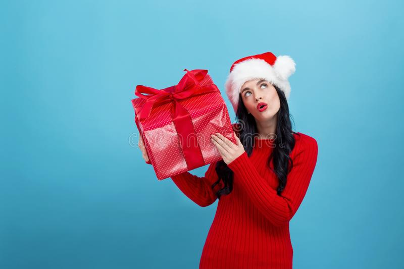Young woman with santa hat holding a gift box royalty free stock photos