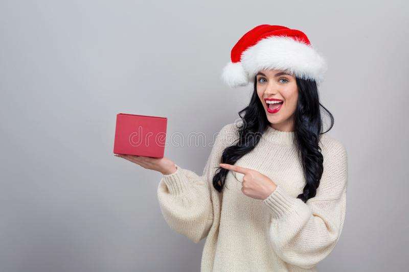 Young woman with santa hat holding a gift box. On a gray background royalty free stock photo
