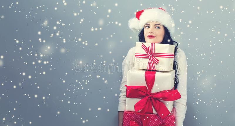 Young woman with santa hat holding gift boxes. On a gray background royalty free stock photos
