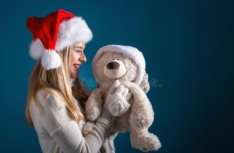 Young woman with santa hat holding a teddy bear royalty free stock photos