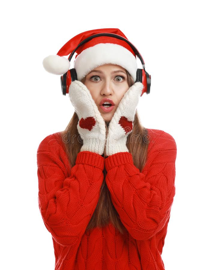 Young woman in Santa hat listening to Christmas music on background stock photos