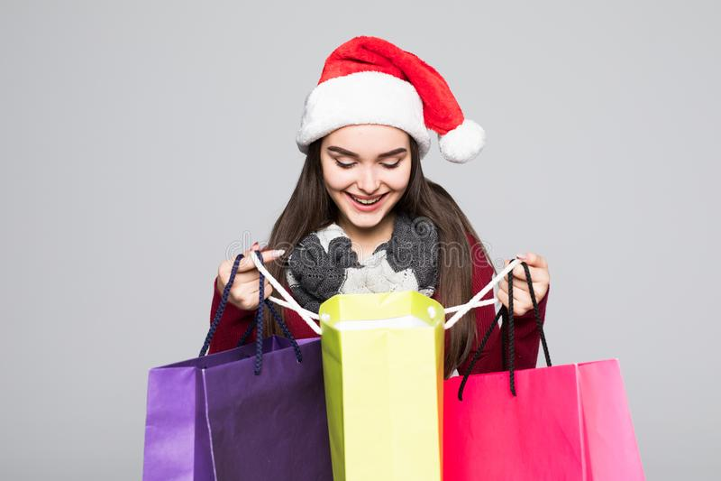 Young pretty woman in santa hat with shopping bags on grey background royalty free stock images