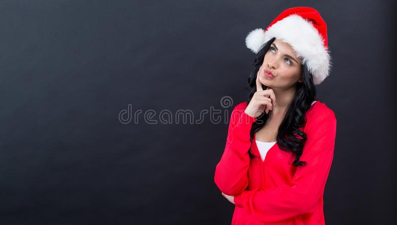 Young woman with Santa hat thoughtful pose royalty free stock images