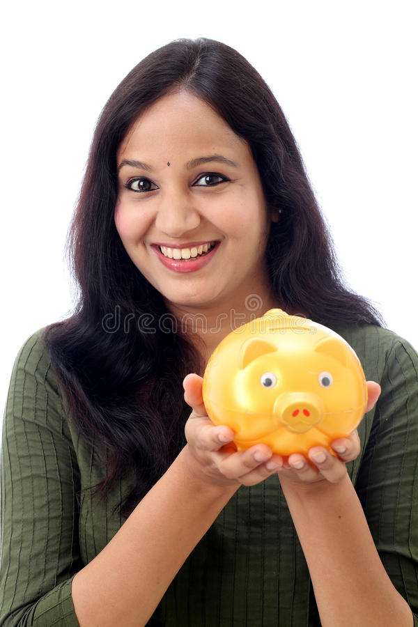 Young Woman Saves Money in Piggy bank. Young Indian Woman Saves Money in Piggy bank royalty free stock image