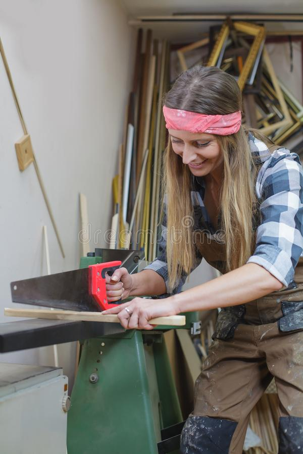 Young woman sawing wooden slat. Young woman cutting wooden slat royalty free stock images