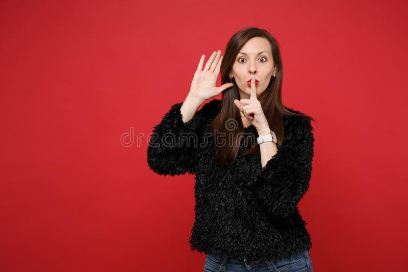Young woman saying hush be quiet with finger on lips shhh gesture, eavesdrop hearing with hand near ear isolated on red. Wall background. People sincere stock photography