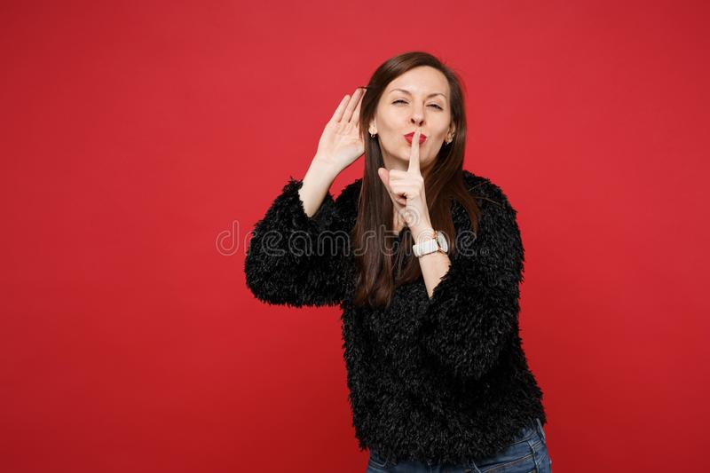 Young woman saying hush be quiet with finger on lips shhh gesture, eavesdrop hearing with hand near ear isolated on red. Wall background. People sincere stock image