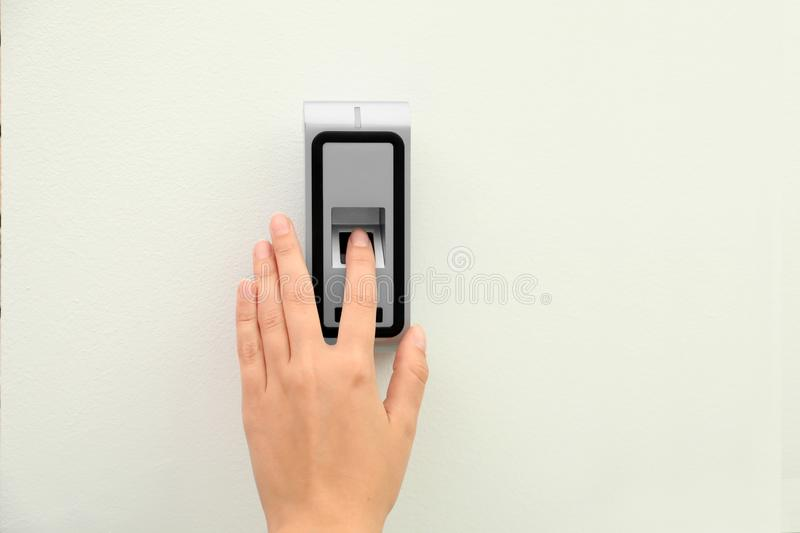 Young woman scanning fingerprint on alarm system. Indoors royalty free stock image