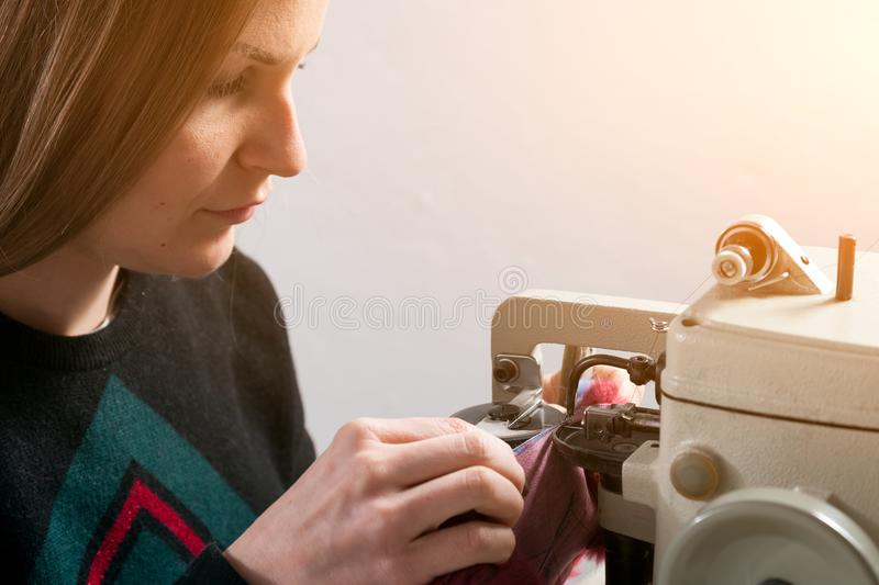 Young woman skinner. A young woman scinner, furrier sews a bright fur coat of natural blue fur on sewing machine stock image