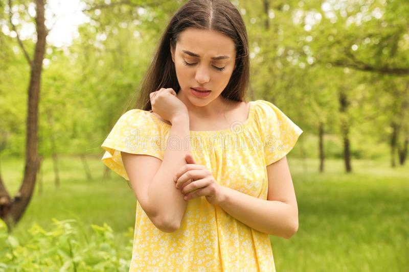 Young woman scratching hand. Seasonal allergy royalty free stock image