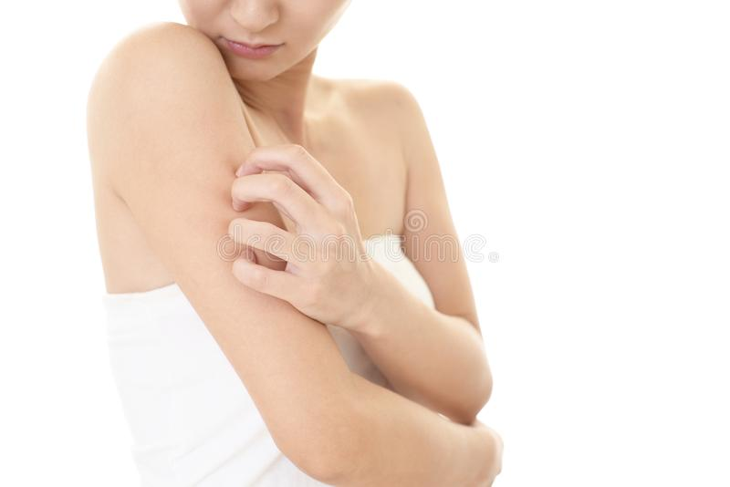 Woman scratching her itchy arm with allergy rash royalty free stock image