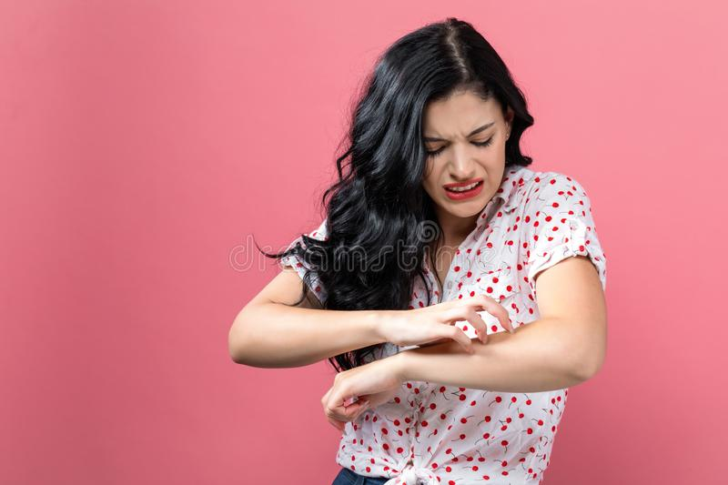 Young woman scratching her itchy arm. Skin problem royalty free stock images