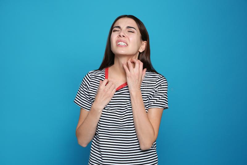 Young woman scratching neck on color background stock photo