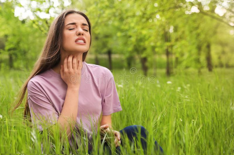 Young woman scratching neck outdoors. Seasonal allergy. Young woman scratching neck outdoors, space for text. Seasonal allergy royalty free stock images