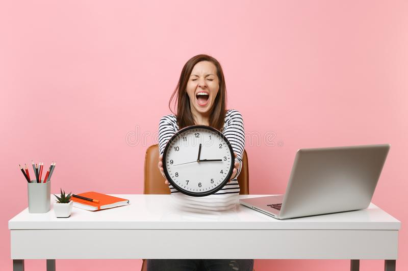 Young woman screaming holding round alarm clock while sit, work at white desk with pc laptop isolated on pastel pink stock photos